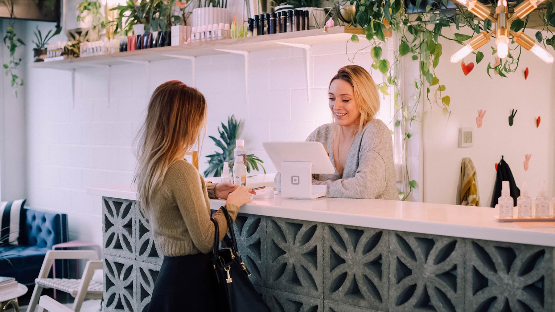 En kvinna betalar vid disken i en mindre butik.